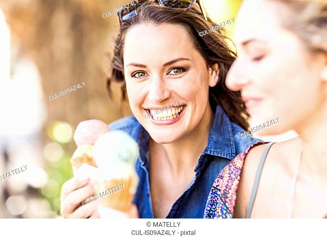 Friends holding ice cream cone smiling