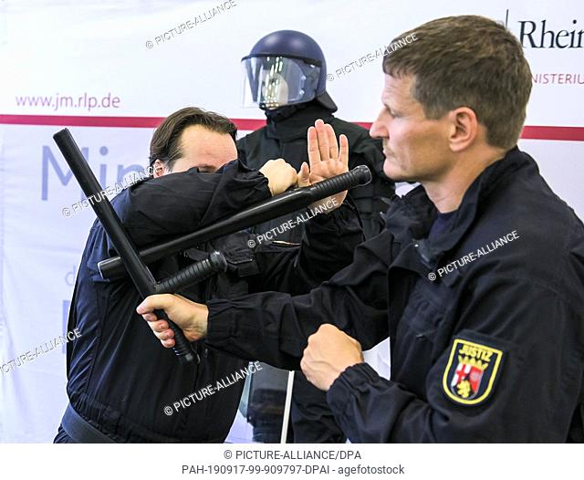 16 September 2019, Rhineland-Palatinate, Mainz: At a press conference at the Ministry of Justice, prison officers John Klein (l) and Martin Bronder demonstrate...