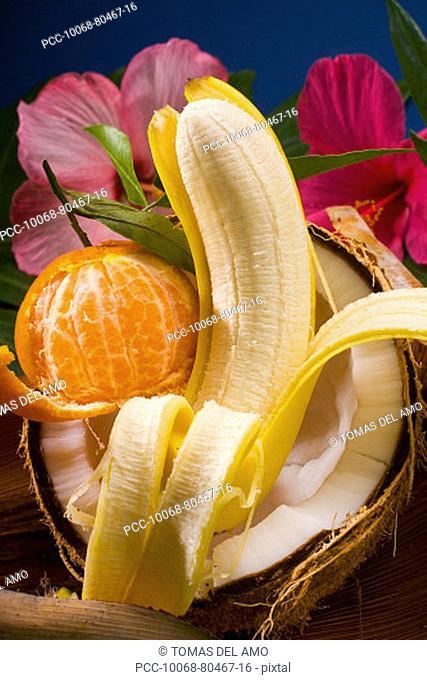 Studio shot of a cracked coconut, a peeled tangerine and a peeled banana
