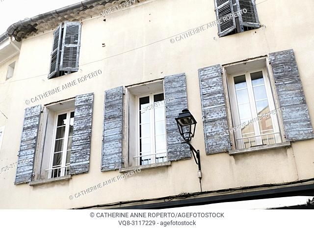 Sun weathered, pale blue rustic shutters on a traditional Provencal house with carriage lamp in L'Isle-sur-la-Sorgue, Provence, France