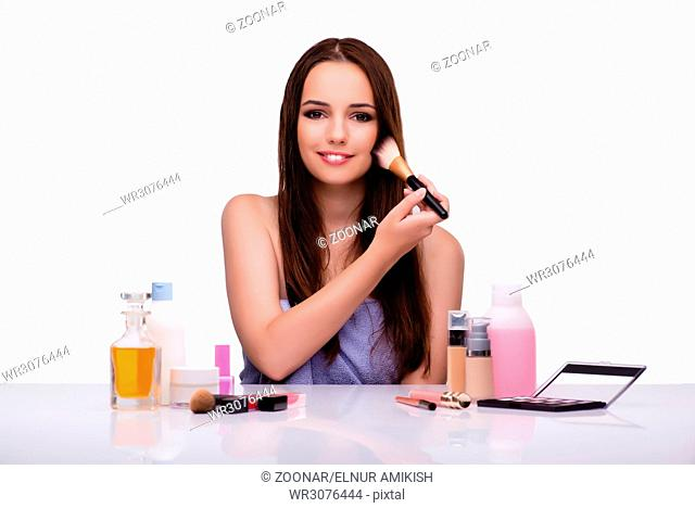 Woman doing makeup isolated on white