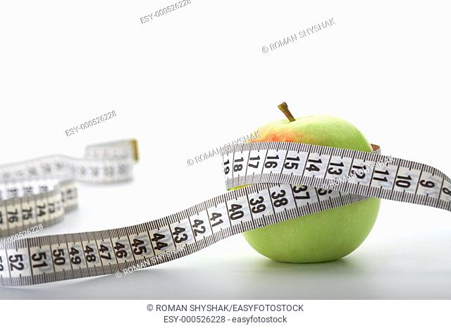 Apple with a measuring tape on white