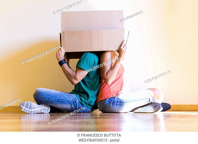 Couple with heads in cardboard box sitting back to back on the floor at new home