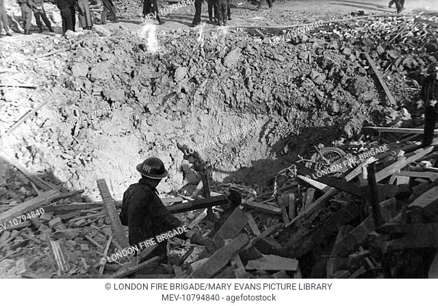 A bomb crater in Minington(?) Road, Leyton, East London, during the Second World War, 22 October 1944