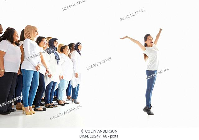 Portrait of woman standing out from the crowd and celebrating