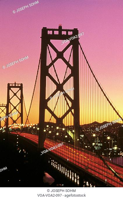 This is the Bay Bridge at sunset. There is a pink and orange glow in the sky