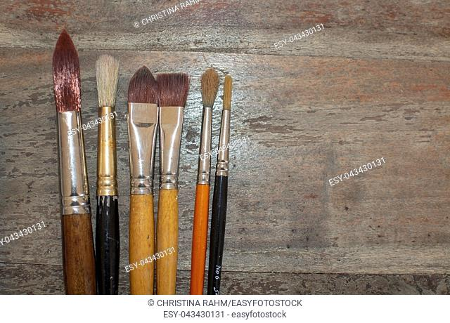 Set of various artist brushes for watercolor painting on old shabby grungy retro vintage wooden background