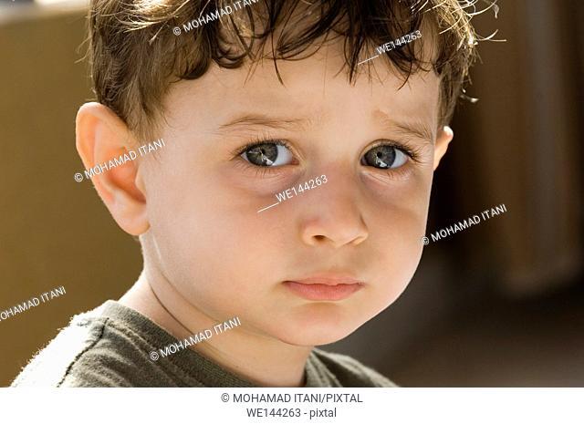 Sad 2 years old boy looking at the camera