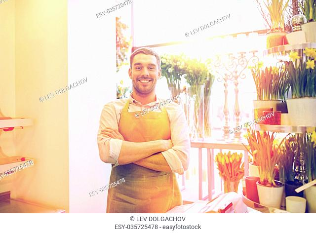 people, sale, retail, business and floristry concept - happy smiling florist man or seller standing at flower shop counter