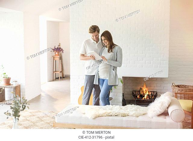 Pregnant couple using digital tablet near fireplace