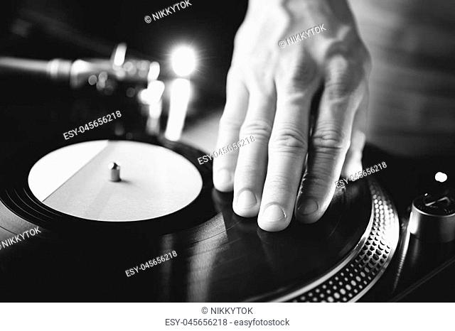 turntable scratch, hand of dj on the vinyl record, black and white