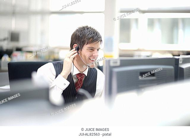 Businessman using headset at desk