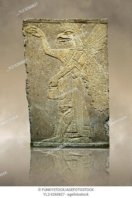 Assyrian relief sculpture panel of a protective spirit with an eagles Head from Nimrud, Iraq. The spirit is holding a symbolic fir cone and is sprinkling holy...