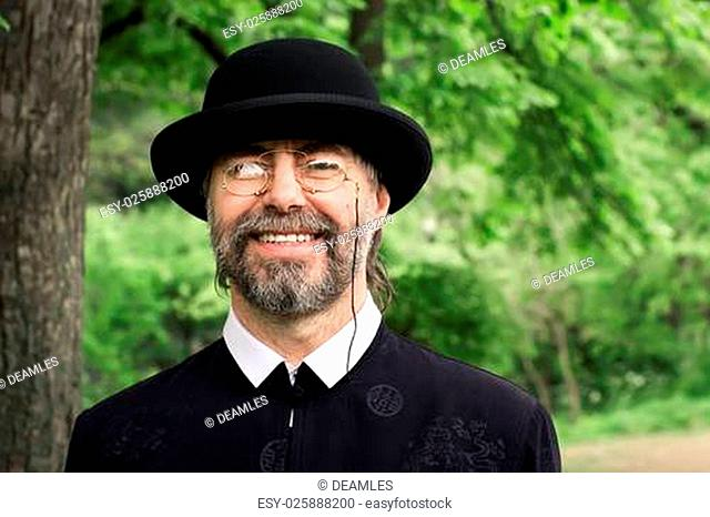 Portrait of a retro styled senior, wearing a suit and hat, as well as old fashion eyeglasses. Outdoors