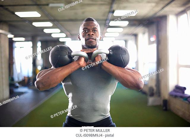 Man lifting kettlebells in gym