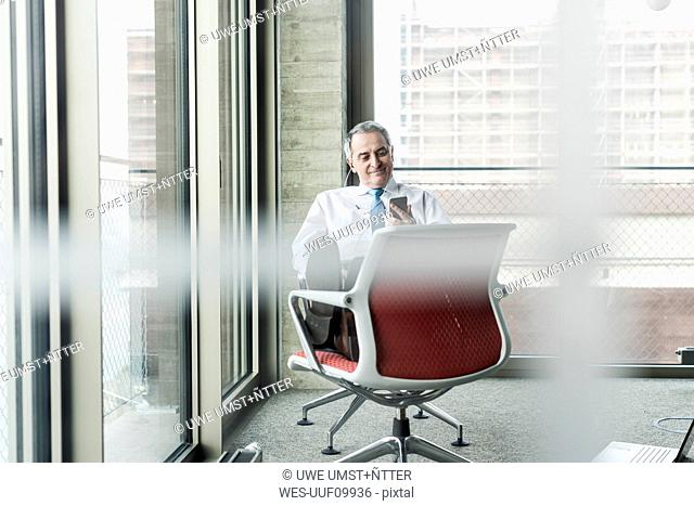 Senior manager in office sitting on chair talking on the phone