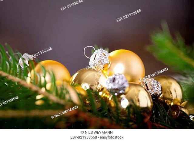 Goldener glänzender Christbaumschmuck Advebtsschmuck auf grünen Tannenzweigen