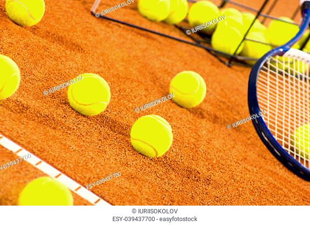 Tennis balls scattered from basket on court