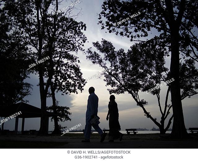 Silhouette of man and woman walking at park, in Singapore