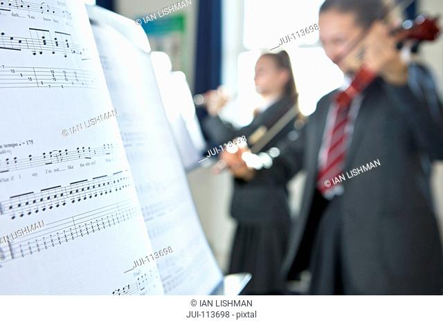 Sheet music in foreground with high school student playing violin