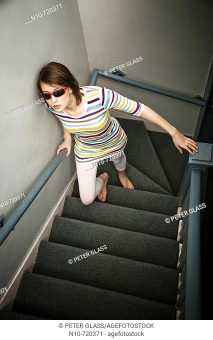 Young woman, wearing sunglasses, climbing her apartment building's stairs