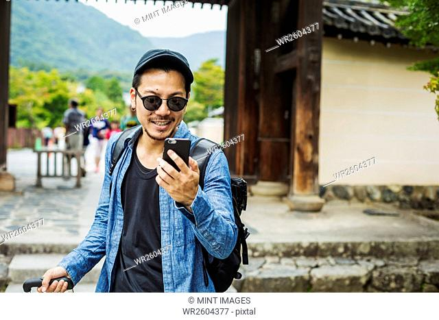 A man in sunglasses looking at his smart phone