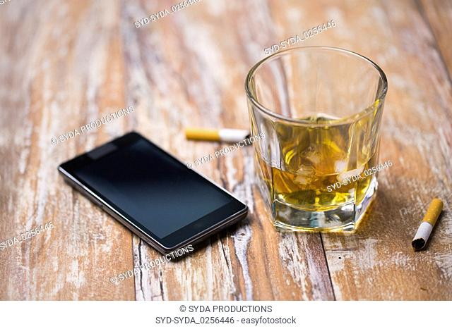 glass of alcohol and smartphone on table