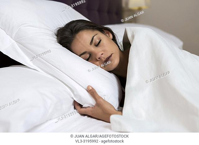Content young brunette under white blanket lying on cozy pillow and sleeping in bed