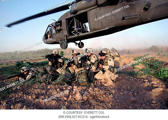 A Quick Response Force brace themselves in a security posture after being dropped off by a Black Hawk helicopter on a mission in Iraq. June 19 2004