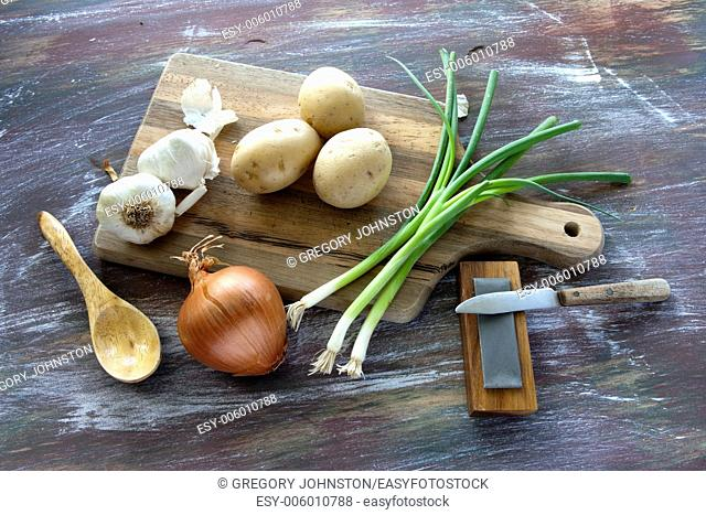 A fine art image of assorted vegetables a cutting board and some utensils