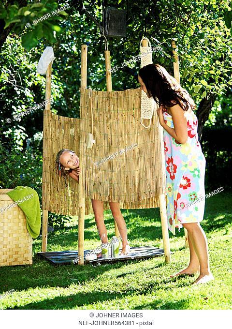 A girl taking a shower in the garden, Sweden