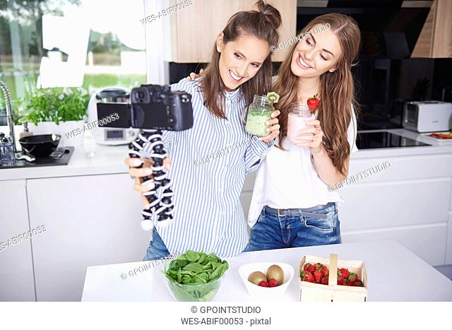 Food bloggers filming theirselves drinking smoothies