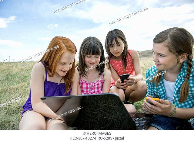 Schoolgirls with technologies sitting on field