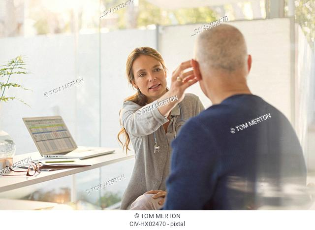 Female doctor helping male patient with hearing aid in doctor's office