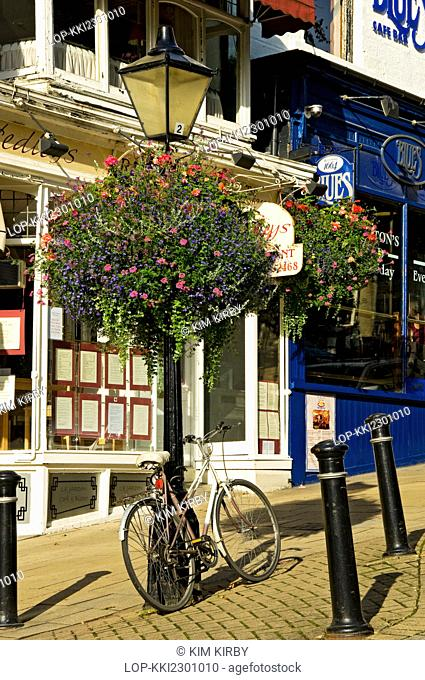 England, North Yorkshire, Harrogate. Bike leaning against a lamp post with a hanging flower basket on Montpellier Parade