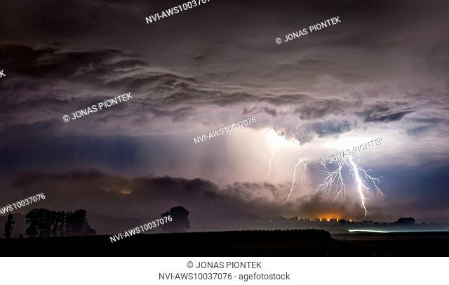 Strong branched cloud-to-ground lightnings behind the foggy mountain of Amöneburg, Hessia, Germany
