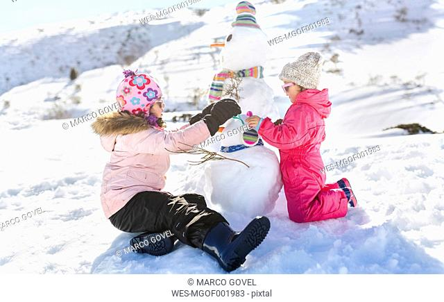 Spain, Asturias, kids playing with snowmen in a snowy mountains