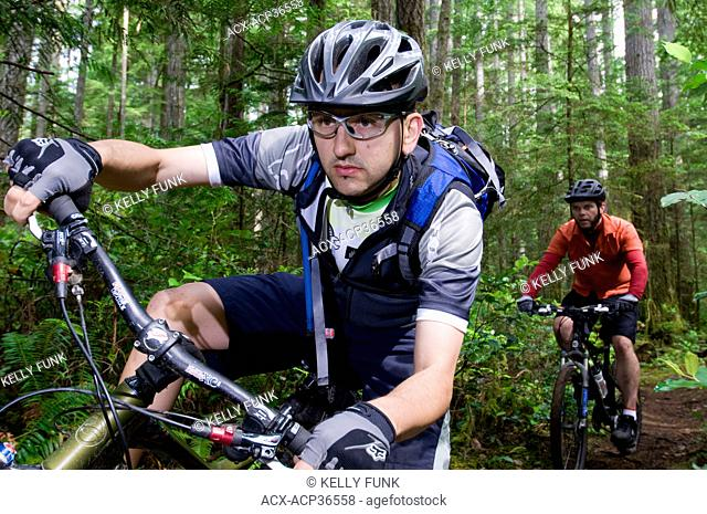 Two male mountain bike riders round a corner near Powell river on the upper Sunshine coast area of the Vancouver coast and mountain range, British Columbia