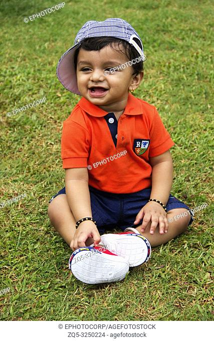 Cute Indian toddler wearing cap, sitting and smiling inside a garden, Pune, Maharashtra