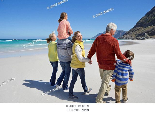 Happy multi-generation family walking on sunny beach