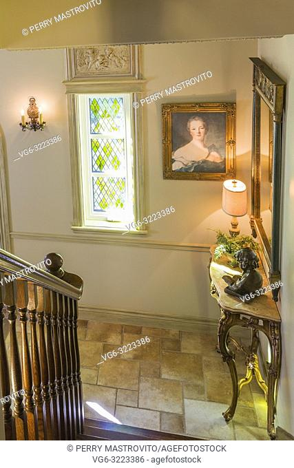 Bottom of brown stained oak wood stairs and antique console with statue and illuminated lamp in main entryway with a leaded stained-glass window inside a 2006...