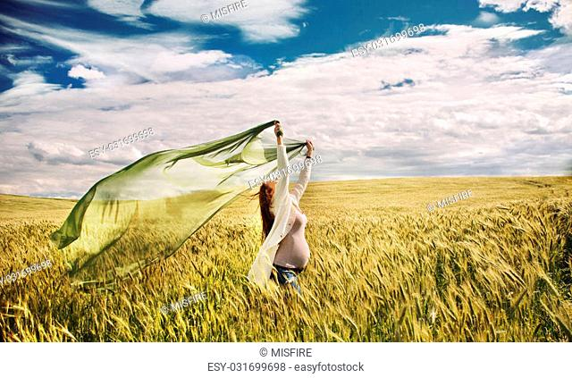 pregnant woman feeling freedom of nature in windy gold field, happy healthy pregnancy