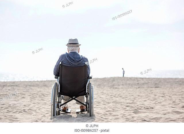 Rear view of senior man in wheelchair looking out from beach, Santa Monica, California, USA
