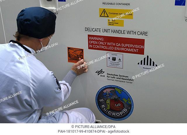 17 October 2018, Bremen: An employee of the German Aerospace Center (Deutsches Zentrum für Luft- und Raumfahrt; DLR) sticks signs on the crate in which the...