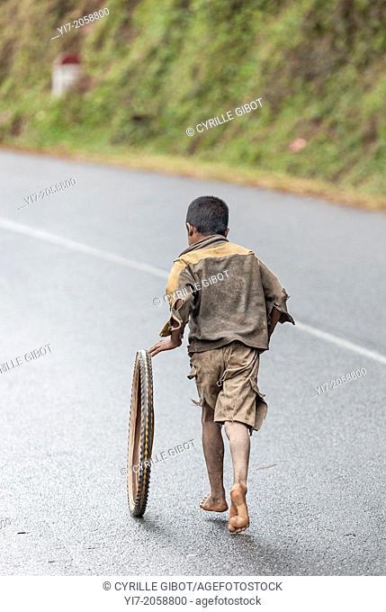 Boy playing with a tire, Ranomafana, Madagascar