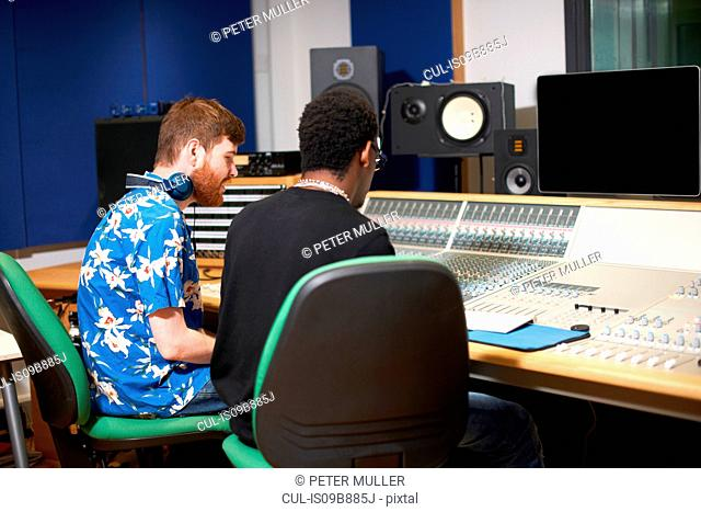 Two young male college students at sound mixer in recording studio