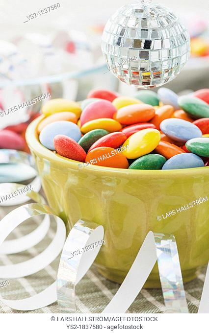 Close up of multicolored candy with streamers and miniature disco ball