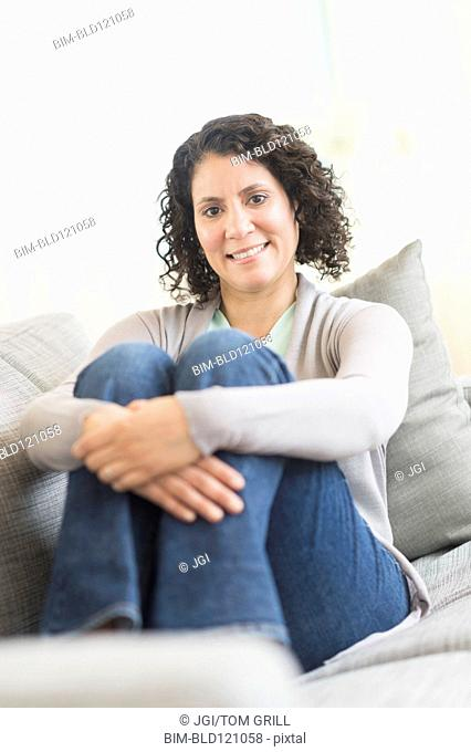 Hispanic woman hugging her knees on sofa