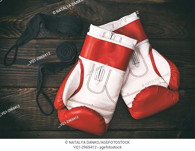 pair of leather red boxing gloves and a black bandage on a brown wooden background