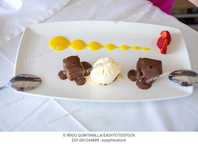 tray with delicious sweet dessert: black chocolate, vanilla ice cream, strawberries and mango sauce, with two spoons in restaurant